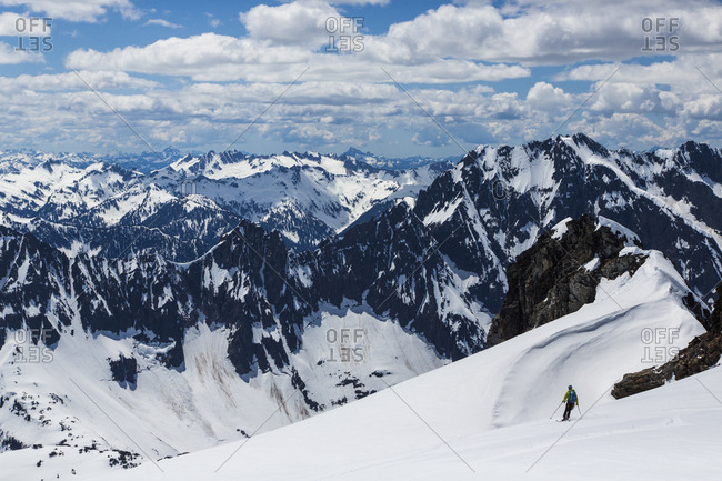 A man skis down a gentle slope off Sahale Peak, a remote mountain in the North Cascades National Park, WA