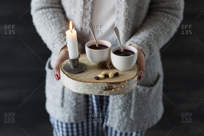Woman holding wooden tray with cups and candle