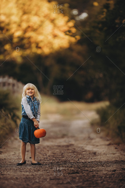 Young girl holding pumpkin on dirt road