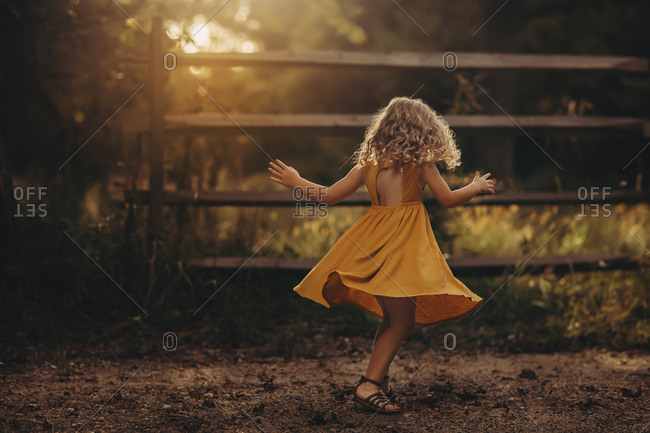 Girl in yellow dress spinning
