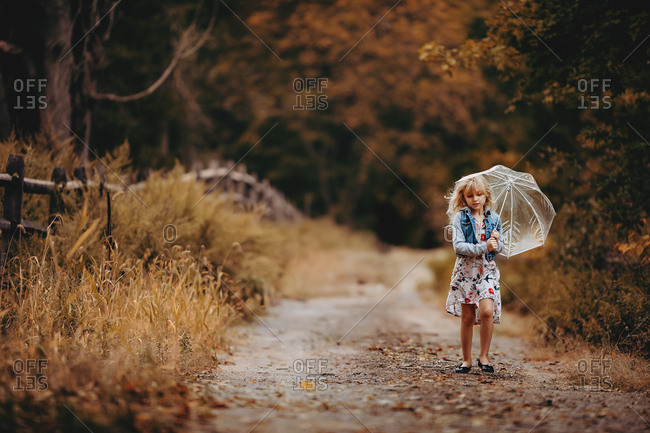 Young girl holding a clear umbrella on a back drive way