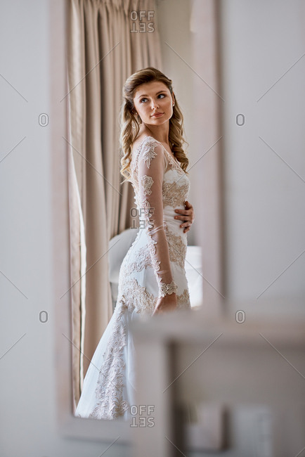 Beautiful bride admiring her wedding dress gown in the mirror