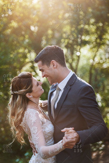 Young married couple smiling dancing under trees with sun flare