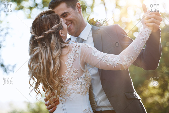Man laughing and smiling at his new wife while dancing