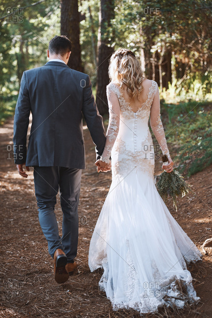 Happy married couple walking together hand in hand after wedding ceremony with sun through trees