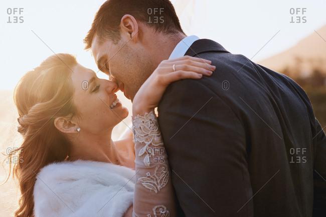 Happy wedding couple kiss outdoors