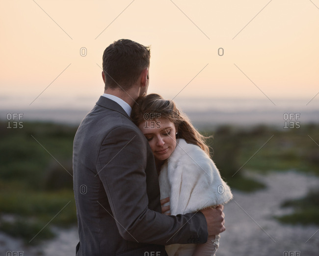 Man in suit hugging woman tenderly on beach at sunset