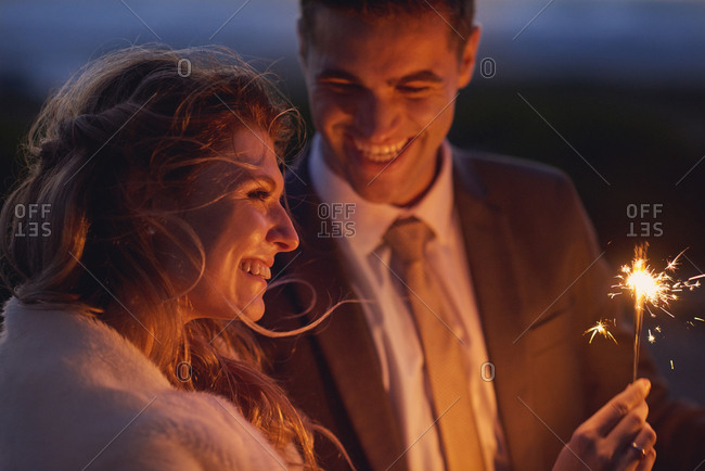 Beautiful couple in gown and suit waving sparklers at sunset