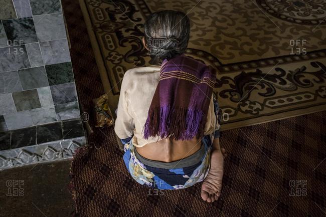Mandalay, Myanmar - 23 September 2016: Woman praying at Mahamuni Paya