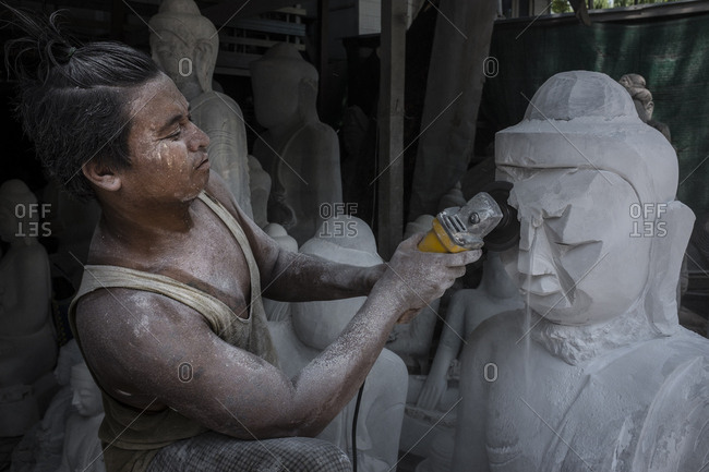 Mandalay, Myanmar - 23 September 2016: Worker making marble Buddha statues