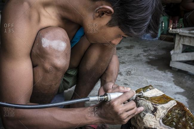 Mandalay, Myanmar - 23 September 2016: Worker polishing a jade stone at Mandalay's Jade Market
