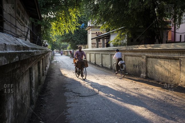 Mandalay, Myanmar - 23 September 2016: People riding bicycles near a Buddhist monastery in a street of Mandalay