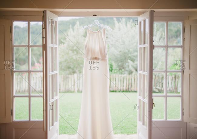 Wedding dress hangs in door at wine estate