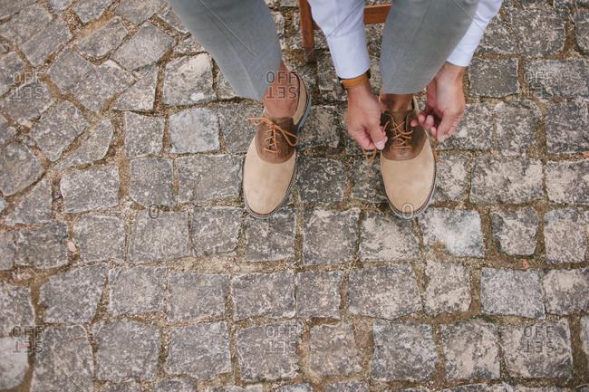 Man ties wedding shoes