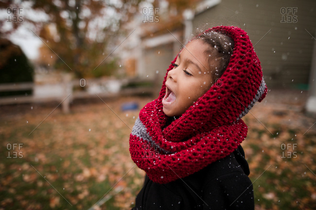 Little girl in knit scarf catching snowflakes