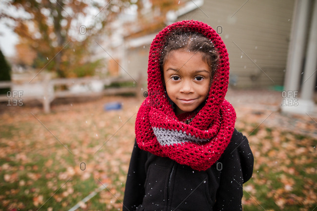 Little girl in knit scarf stands in snow