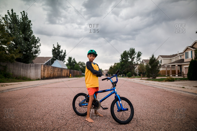 Boy with bicycles in neighborhood