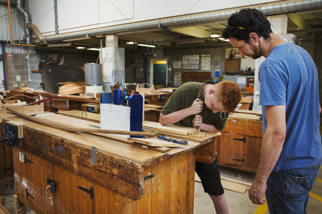 Two men standing at a workbench in a boat-builder's workshop, working on wooden joint