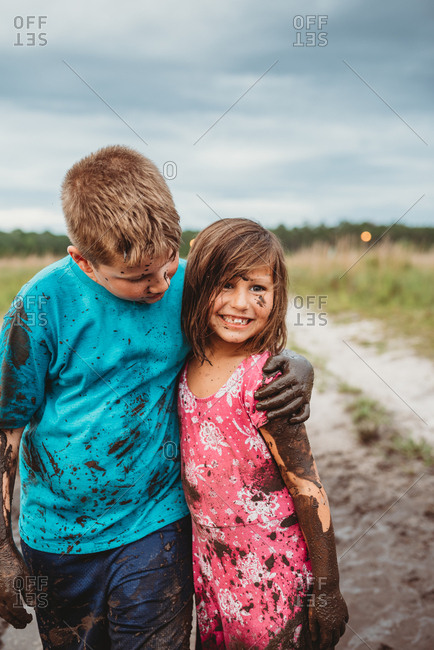 Siblings play in muddy field