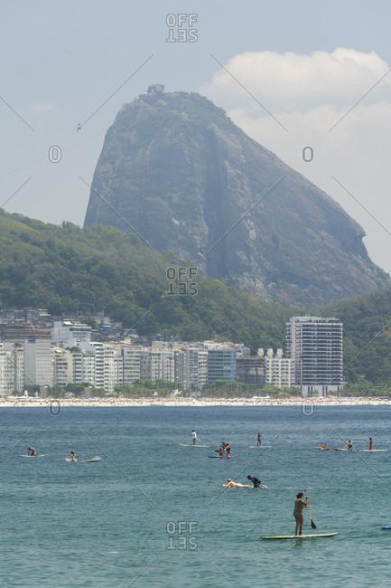 October 23, 2017: People enjoying a sunny day on a Stand Up Paddle board in Praia de Copacabana, Rio de Janeiro, Brazil