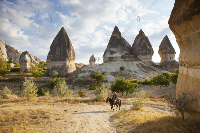 October 23, 2017: A female traveling on the back of a horse between the famous fairytale chimneys (rock formations) of Cappadocia, Turkey. Cappadocia means Land of the beautiful horses. The region is closely connected to the equine, with historic finds describing in imagery how its peoples tendered their horses and formed the bedrock of its international reputation.