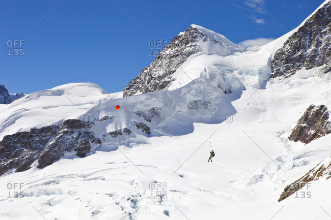 October 23, 2017: A female is flying high in the sky above the glacier on the zip line at the Jungfraujoch near Grindelwald in the Swiss Alps.