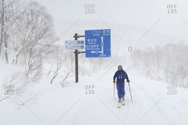 October 23, 2017: A man is ski touring over a snow covered road near Niseko on Hokkaido, Japans northern Island, famous for winter sports. In winter times some roads are closed because it is nearly impossible to remove the big amounts of snow that fall yearly.