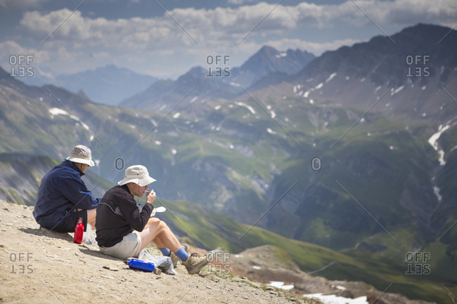 July 11, 2015: Two hikers is are having lunch on the ridge of the Tete des Fours with Mont Blanc valley in the distance. This is halfway the Tour du Mont Blanc, a classic multi day hike around the highest peak of the Alps.