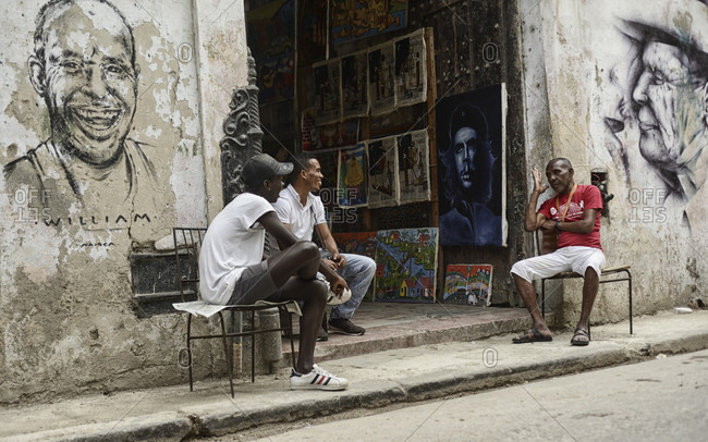 February 4, 2017: Men talk outside of an art shop in Havana, Cuba.