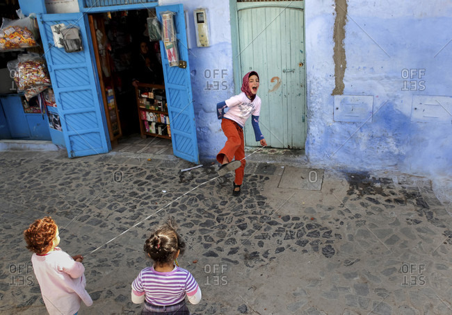 March 16, 2012: A girl laughs while she plays a skipping game with some friends in Chefchaouen, Morocco, whose medina (old city) is famous for its striking blue walls.