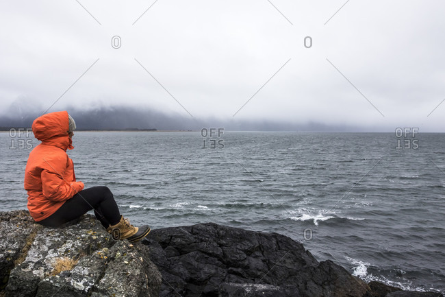 April 12, 2015: Professional Snowboarder Robin Van Gyn sits on a rock and looks over the ocean on a stormy down day while on snowboard trip to Haines, Alaska.