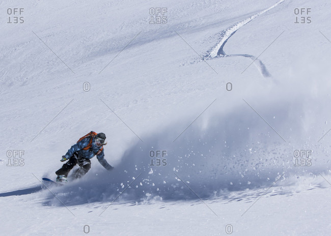 April 13, 2015: Professional Snowboarder Robin Van Gyn, rides fresh powder on a sunny day while snowboarding in Haines, Alaska.