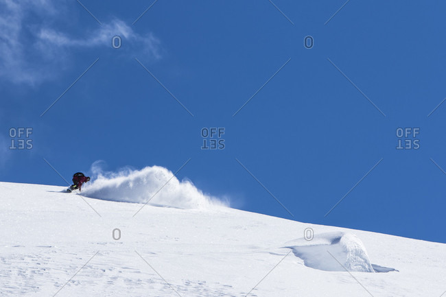April 13, 2015: Professional Snowboarder Helen Schettini, rides fresh powder on a sunny day while snowboarding in Haines, Alaska.