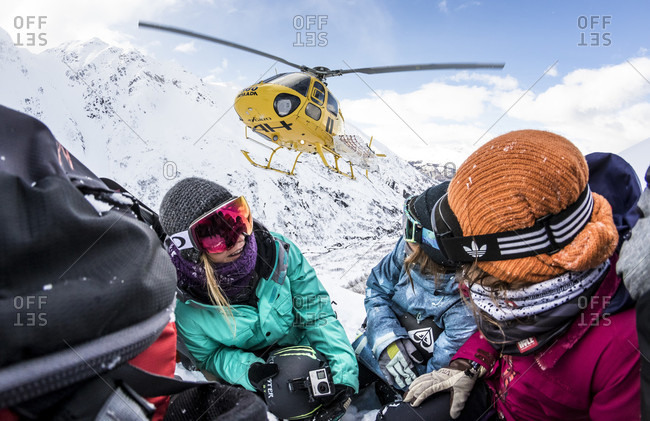 April 17, 2015: Professional snowboarders Helen Schettini, Jamie Anderson, and Robin Van Gyn, crouch down as a helicopter comes in to land next to them on a sunny blue bird day in Haines, Alaska.