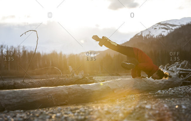 April 17, 2015: Professional Snowboarder Helen Schettini does a yoga on a log after a long day of riding in Haines, Alaska.