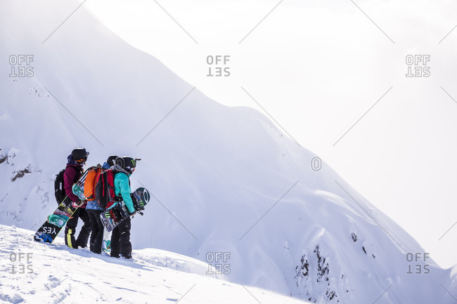 April 17, 2015: Professional snowboarders Robin Van Gyn, Helen Schettini, and Jamie Anderson, stand on a ridge and look down at a line they are about to ride on a sunny day in Haines, Alaska.
