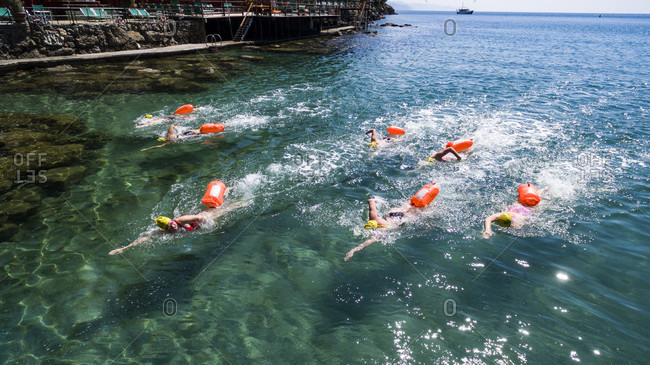 May 6, 2016: group of seven young swimmerseach with a life buoytraining in the clear and transparent waters of the Ligurian sea with terrace and pontoon behind them and a boat in the background on a sunny day in Paraggi, Cinque Terre, Italy