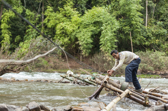 January 14, 2014: A man adjusts the micro hydro turbines in the flow of the Nam Ou River at Ban Sop Kha, Laos. The turbines are used by villages all along the river to generate electricity, at least during the dry season when the water level is low enough to mount them to the river bed.