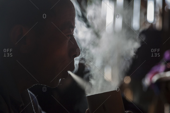 January 14, 2014: A man smokes a cigarette through a large bamboo water bong at his home in Ban Sop Kha, Laos. The man explained that smoking cigarettes this way was better for his lungs.