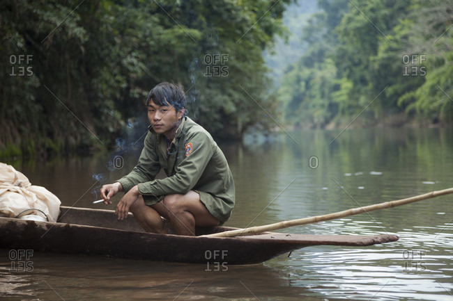 October 23, 2017: A young man on a hunting and fishing expedition smokes a cigarette in his dugout boat on the Nam Ou River, Laos.