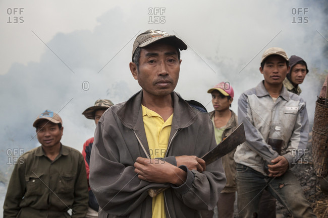 January 20, 2014: Men stand in wait with machetes as brush fires burn on the hillside above Muang Va, Laos where villagers are temporarily relocating their homes. The existing town will be completely inundated by Nam Ou River Dam #6 and the government provided resettlement near Hat Sa will not be completed in time.