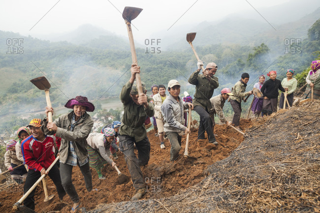 January 19, 2014: Villagers grade a flat foundation for a building on the hillside above Muang Va, Laos, a temporary relocation site for their homes. The town will be completely inundated by Nam Ou River Dam #6 and the government provided resettlement near Hat Sa will not be completed in time.