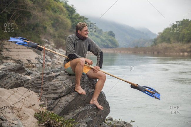 October 23, 2017: Jan, from the Netherlands, poses with his bamboo and flipper paddle at this campsite on the shore of the Nam Ou River, Laos. He ultimately paddled from Muang Khua to Nong Khiaw on a bamboo raft he had constructed with the input of locals.
