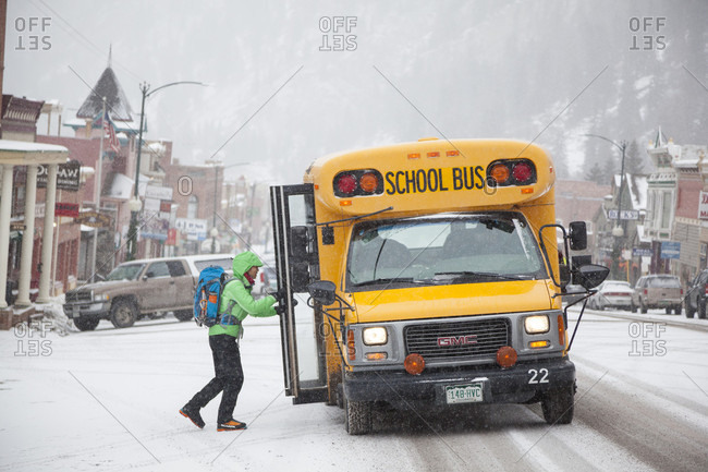 January 15, 2016: A woman on Main Street boards the school bus shuttle to the Ice Park during the Ouray Ice Festival in Ouray, Colorado.