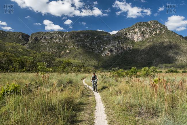 Woman riding adventure bike in Serra do Cipo National Park, Minas Gerais, Brazil