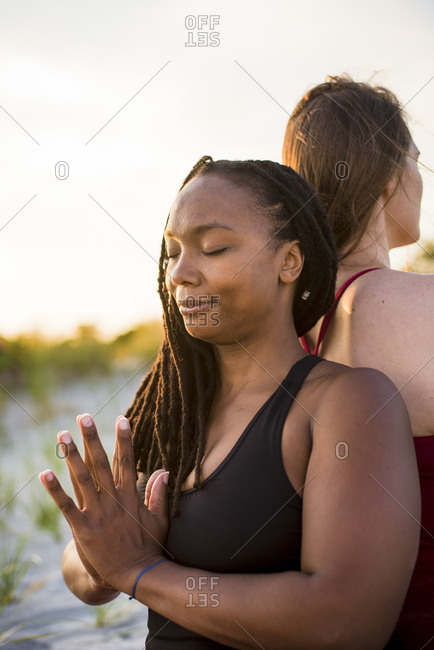 Woman mediating with hands clasped (Anjali mudra), Newport, Rhode Island, USA