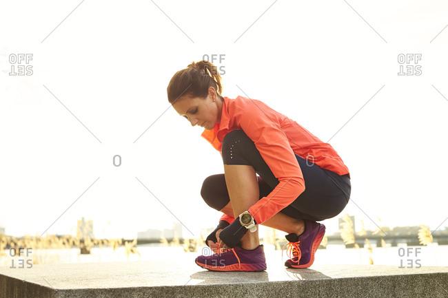 Female jogger tying shoes against clear sky, Boston, Massachusetts, USA