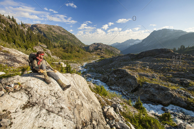A mountaineer sits on a boulder above a rushing river, Garibaldi Provincial Park