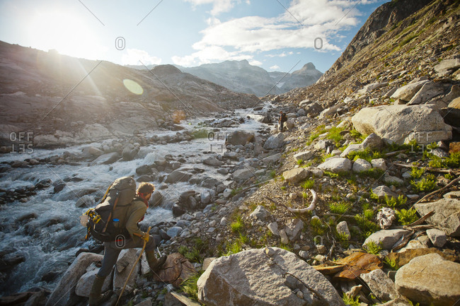 A mountaineer catches up to his friend alongside a rushing mountain stream.