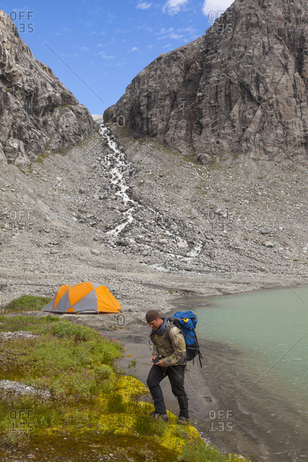 A hiker leaves his lakeside mountain campsite, Garibaldi Provincial Park
